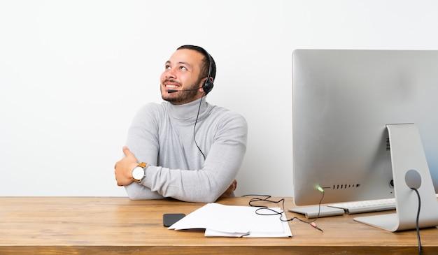 Kolumbianischer mann des telemarketers, der oben beim lächeln schaut