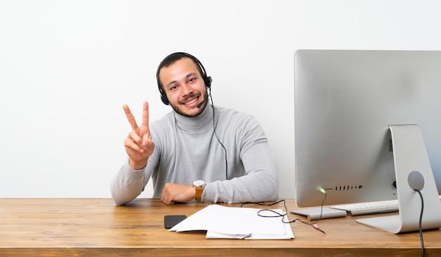 Kolumbianischer mann des telemarketers, der siegeszeichen lächelt und zeigt