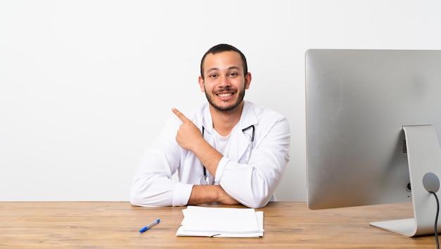 Kolumbianischer mann doktors, der auf die seite zeigt, um ein produkt darzustellen