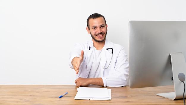 Kolumbianischer mann doktors, der hände für das schließen viel rüttelt