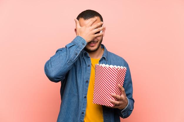 Kolumbianischer mann mit den popcorns, die augen durch hände bedecken