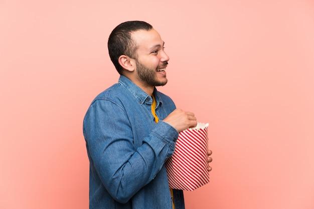 Kolumbianischer mann mit popcorn über getrenntem rosa