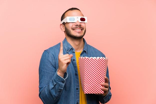 Kolumbianischer mann mit popcorn zeigt mit dem zeigefinger eine großartige idee