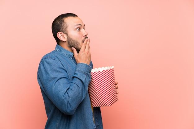 Kolumbianischer mann mit popcornsover lokalisierte rosa hintergrund