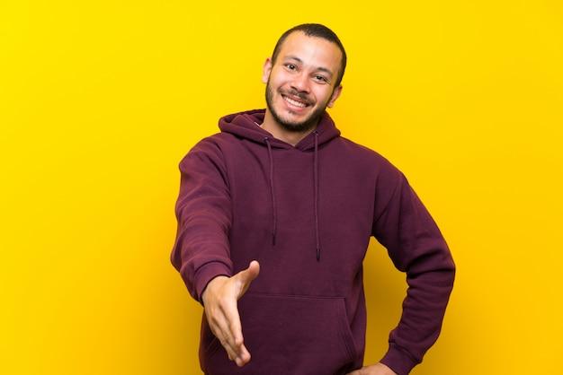 Kolumbianischer mann mit sweatshirt über der gelben wand, die hände für das schließen viel rüttelt