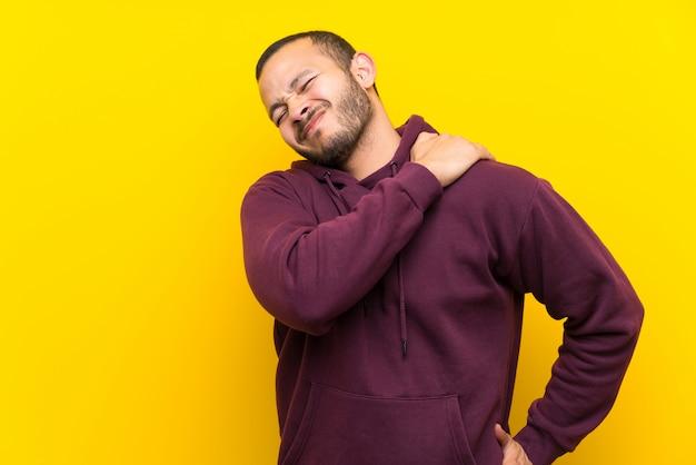 Kolumbianischer mann mit sweatshirt über gelber wand, die unter den schmerz in der schulter leidet, weil sie sich bemüht hat