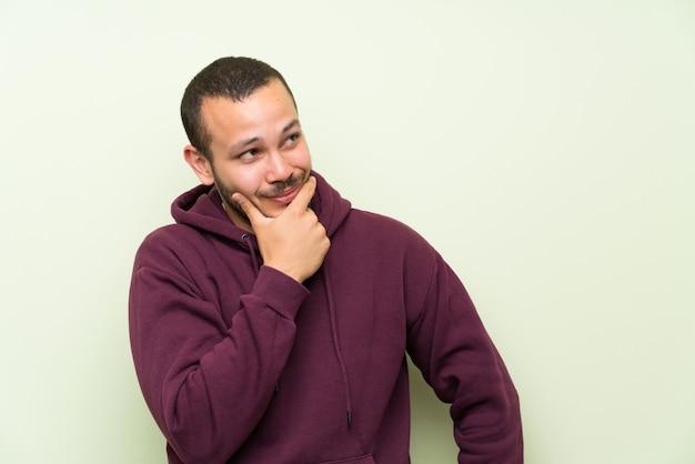 Kolumbianischer mann mit sweatshirt über grüner wand eine idee denkend