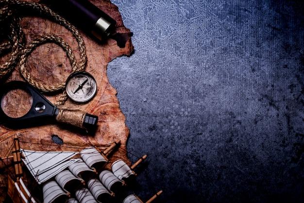 Kolumbus-tag. piraten und schätze mit weltkarte und entdeckungsausrüstung. kopieren sie platz auf dunklem hintergrund.