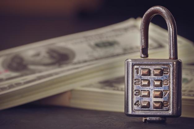 Kombinationsvorhängeschloß und dollarbanknote in der dunkelheit. konzept von geschäftsgeheimnissen oder von finanzieller sicherheit.