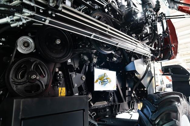 Kombinieren sie von innen einen servicemonitor für die reparatur und wartung von landmaschinen. moderne autowerkstatt für den landwirt.
