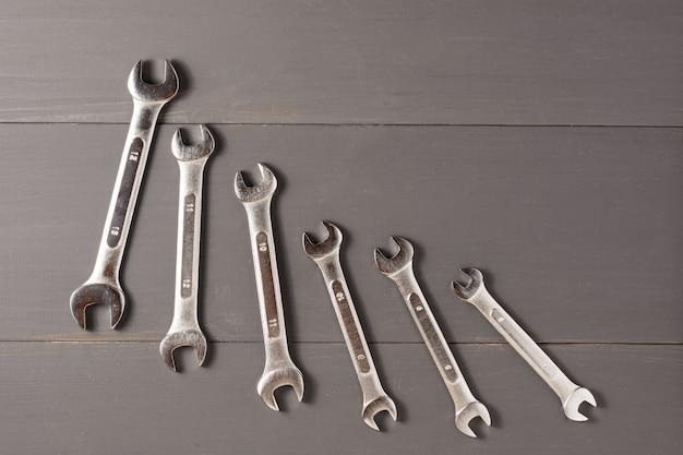 Kombinierte schlüssel, um das auto auf dem grauen tisch in abnehmender reihenfolge zu reparieren. der blick von oben. ein flaches bild