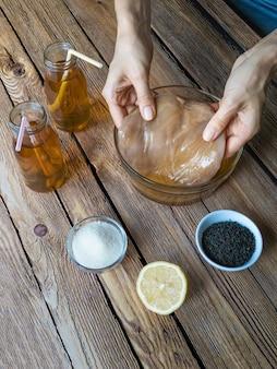 Kombucha durch fermentation von tee mit symbiotischer kultur von bakterien und hefen auf holztisch.