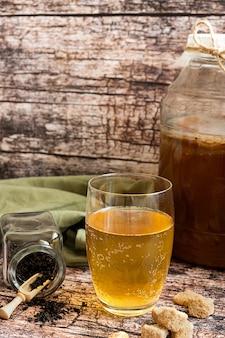 Kombucha fermentiertes gesundes getränk, serviert in einem glas auf einem rustikalen tisch mit zutaten