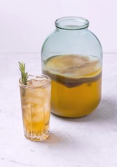 Kombucha in einem glasgefäß und einem glas mit eis gesundes getränk