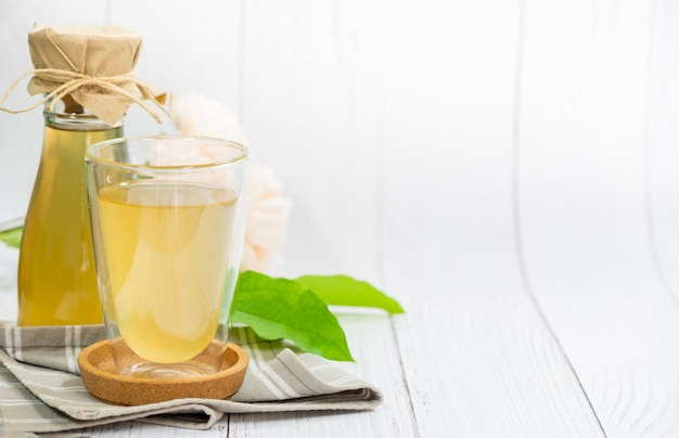 Kombucha-tee mit tiliacora triandra oder bambusgrasblatt, apfelwein fermentiertes getränk. vorteile von kombucha-tee sind quelle von probiotika, reich an antioxidantien und enthält vitamine und mineralien.