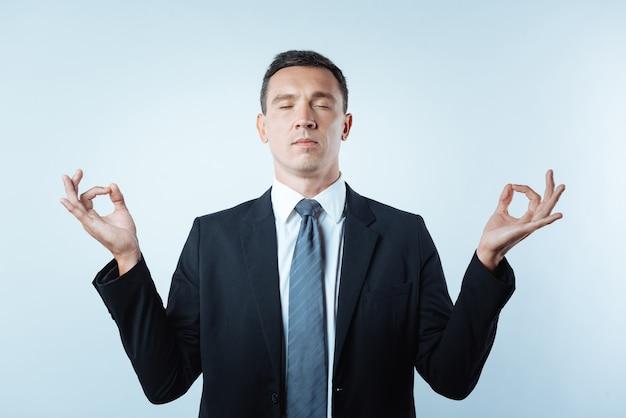 Komfort und frieden. netter hübscher friedlicher mann, der seine augen schließt und meditiert, während er versucht, sich zu entspannen