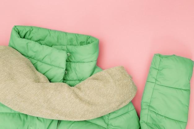 Komfort weibliches warmes winteroutfit für kaltes wetter. helle daunenjacke, gestrickter wollschal. frauenkleidung neo mint trendfarbe. draufsicht. flach liegen.