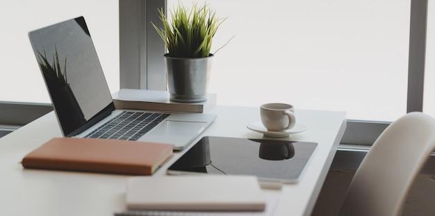 Komfortable home-office-ecke mit laptop, tablet und büromaterial mit kaffeetasse