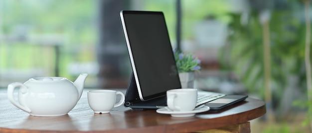 Komfortabler arbeitsbereich mit mock-up-tablet mit leerem bildschirm und tastatur mit keramik-teekannenset
