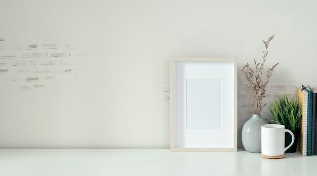 Komfortabler arbeitsbereich mit weißem bilderrahmen und büromaterial auf weißem tisch