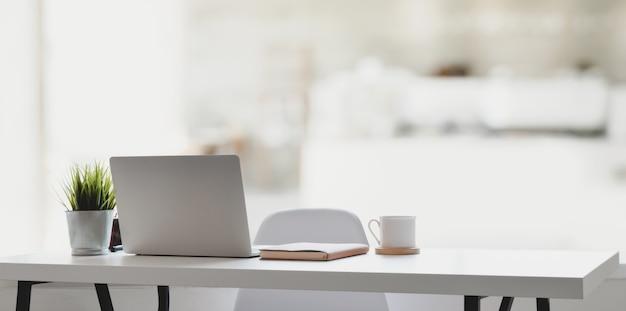 Komfortabler arbeitsplatz mit laptop, kaffeetasse und büromaterial