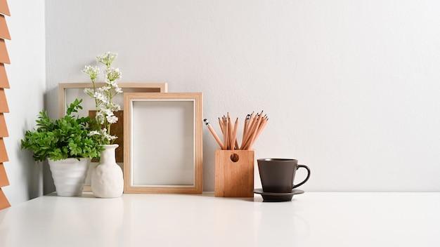 Komfortabler arbeitsplatz mit leerem rahmen, bleistifthalter, kaffeetasse und zimmerpflanze auf weißem tisch.