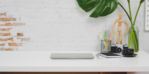 Komfortabler designerarbeitsplatz mit kamera, laptop und büromaterial