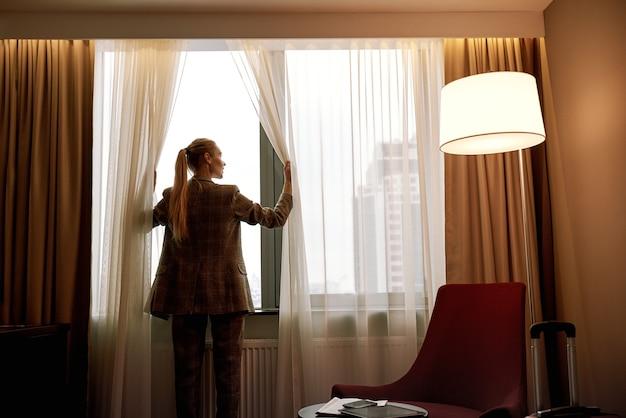 Komfortables hotelzimmer. geschäftsfrau im dunklen hotelzimmer öffnet vorhänge am fenster zum morgenlicht