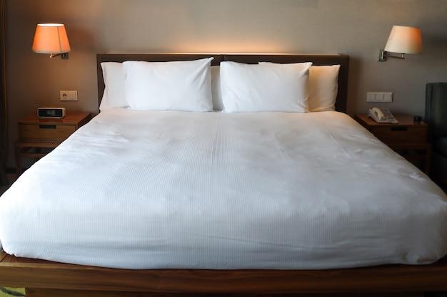 Komfortables schlafzimmer mit aufgeräumtem weißem bett und leselampe auf beiden seiten