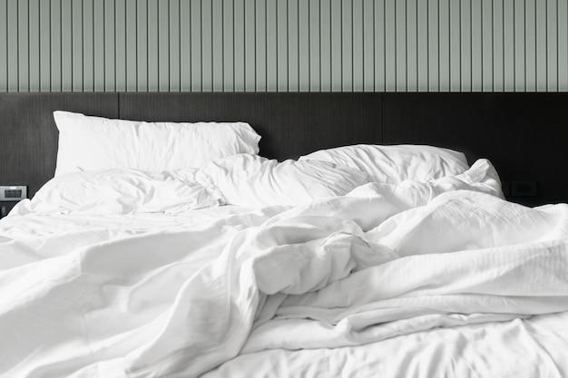 Komfortables schlafzimmer unordentlich weiße bettwäsche und bettdecke unordentlich im schlafzimmer