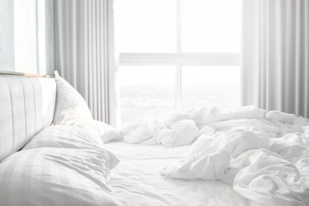 Komfortables schlafzimmer, unordentliche bettwäsche und bettdecke