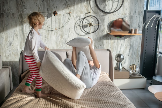 Komische schlacht. kind im pyjama stehender angreifer mit kissen auf verteidigendem liegendem vater zu hause auf bett
