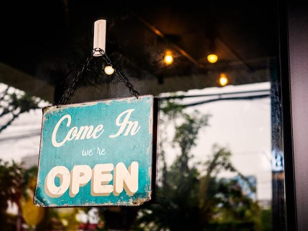 Komm herein, wir sind offenes zeichen auf tür des cafés.