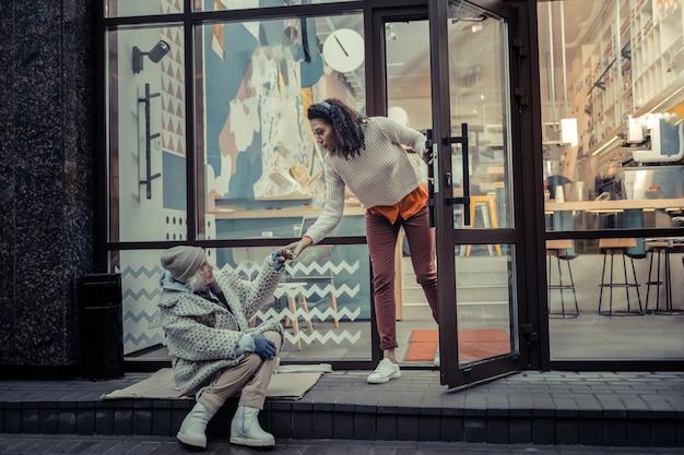 Komm mit mir. schöne junge frau, die eine hand einer netten armen frau nimmt, während sie sie einlädt, hereinzukommen