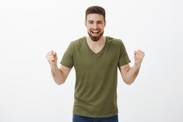 Komm schon, du kannst es. aktiver und aufgeregter glücklicher gutaussehender mann mit geballten bartfäusten im jubel, unterstützender ermutigender freund, beobachtend, wie das team tore schießt, den sieg feiert, triumphiert