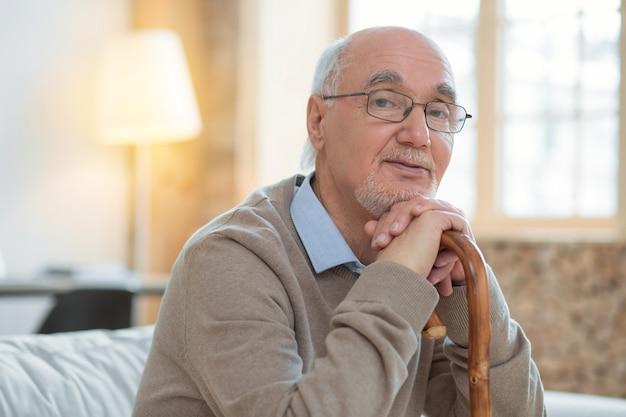 Komm zu mir. meditativer attraktiver älterer mann, der sich auf zuckerrohr stützt, während er brille trägt und kamera betrachtet