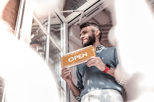 Komm zu uns. niedriger winkel eines netten angenehmen mannes, der nahe der kaffeetür steht, während er ein türschild hält