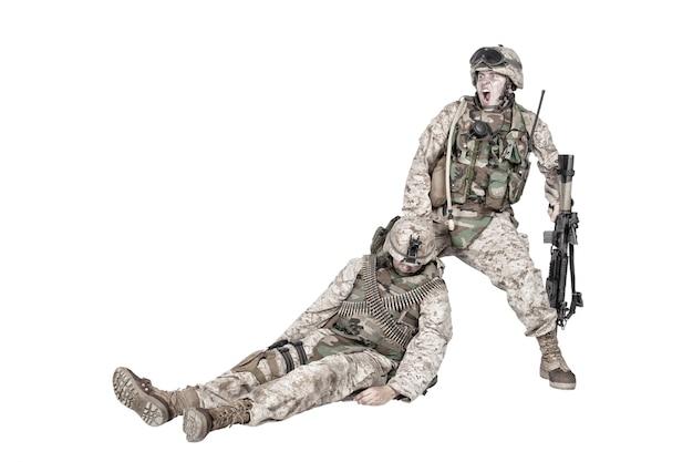 Kommandosoldat schreit und schleift rückwärts für einen verwundeten und bewusstlosen kameraden des plattenträgers. taktische kampfunfallversorgung, verletzter kämpfer, der vom schlachtfeld evakuiert, isoliert auf weiß