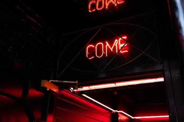 Kommen sie neonlichtzeichen breit durch das glas der tür im café-bar-business-service-konzept