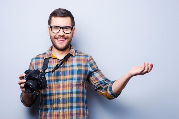 Kommen sie zu mir, um ein gutes foto zu machen. porträt eines selbstbewussten jungen mannes im hemd, der die kamera hält und wegzeigt, während er vor grauem hintergrund steht