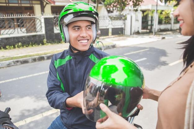 Kommerzieller motorrad-taxifahrer, der seinem kunden helm gibt