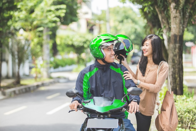 Kommerzieller motorrad-taxifahrer, der seinen passagier nimmt