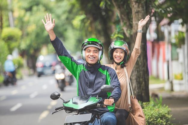 Kommerzieller motorrad-taxifahrer, der seinen passagier zu ihrem ziel bringt