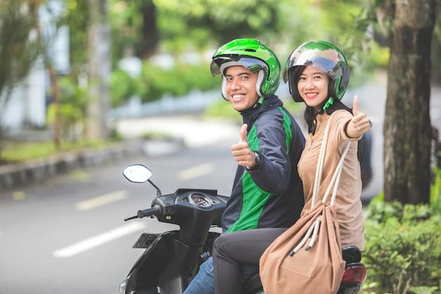 Kommerzieller motorrad-taxifahrer und sein beifahrer zeigen thum