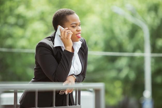 Kommunikation. afroamerikanische geschäftsfrau in bürokleidung lächelnd, sieht selbstbewusst und glücklich aus, beschäftigt. konzept für finanzen, wirtschaft, gleichstellung und menschenrechte. schönes junges weibliches modell, erfolgreich.