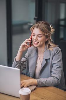 Kommunikation. freudige junge erwachsene blonde frau im geschäftsanzug, der durch smartphone kommuniziert, das am laptop im büro sitzt