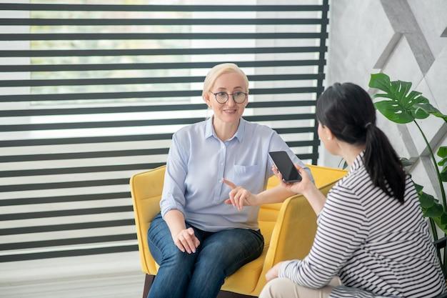 Kommunikation, interviews. erfolgreiche frau in brille und jeans, die auf einem stuhl sitzt und mit ihrer hand gegenüber einer dunkelhaarigen frau mit einem ausgestreckten smartphone gestikuliert.