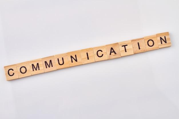 Kommunikation ist ein abstraktes konzept. holzblöcke mit buchstaben lokalisiert auf weißem hintergrund.