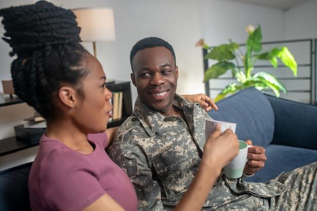 Kommunikation, kaffee. fröhliche geselligkeit dunkelhäutiger frau und militärmann in uniform, die zu hause in gemütlicher umgebung kaffee trinkt