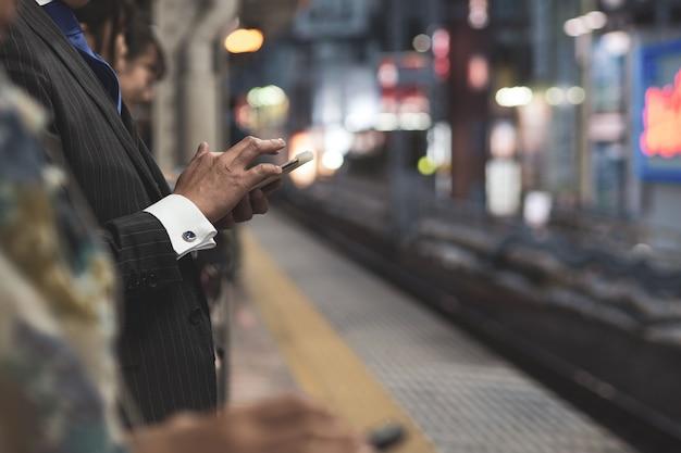 Kommunikation. leute, die handy während auf plattform verwenden